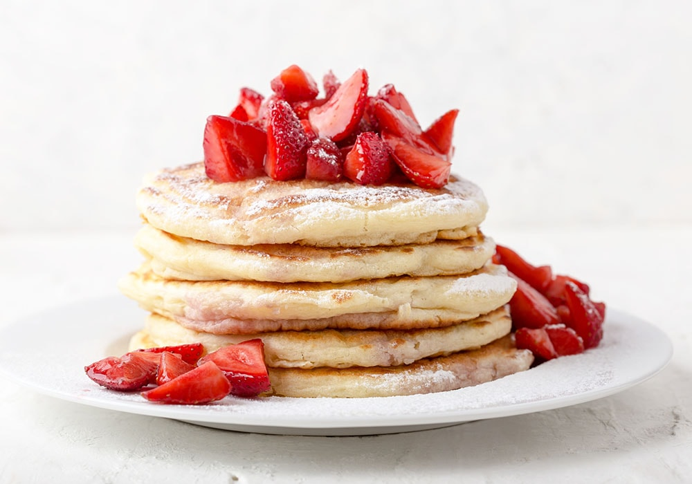 Homemade strawberry  pancakes, fresh summer dessert with strawberries and powdered sugar on white plate