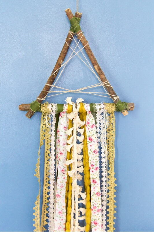 A wall hanging made out of ribbon and yarn.